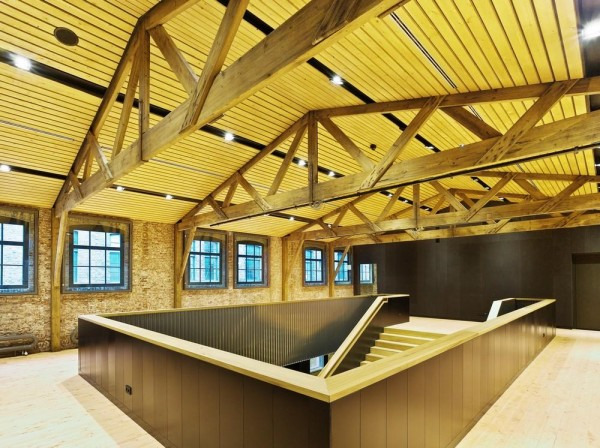 Foyer in the historic factory building with restored wooden rafters and brick walls, Image Courtesy ©  Petra Appelhof