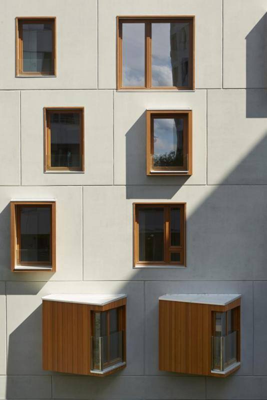 smooth prefabricated walls with wood window frame, Image Courtesy © Frédéric Delangle