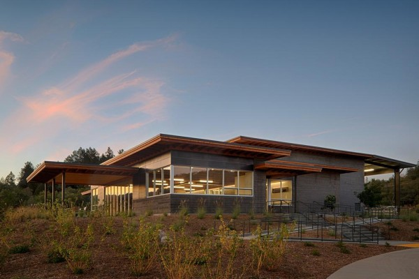 The Southwest corner of Titus Winery is characterized by the covered hospitality area overlooking surrounding vineyards.  Exterior materials include cedar soffits, concrete board-form tilt-up walls, gunmetal blue panels above windows, and anodized aluminum window frames,  Image Courtesy © Technical Imagery Studios