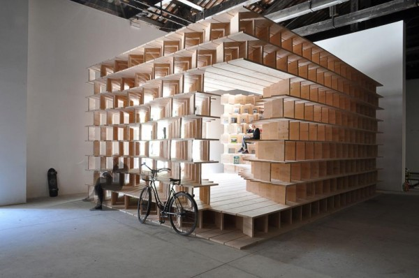 A full-scale spatial structure is generated by a site-specific system of wooden bookshelves that reacts to the given space in Arsenale and home activities in order to be inhabited by the curated books, Image Courtesy © Dekleva Gregorič architects
