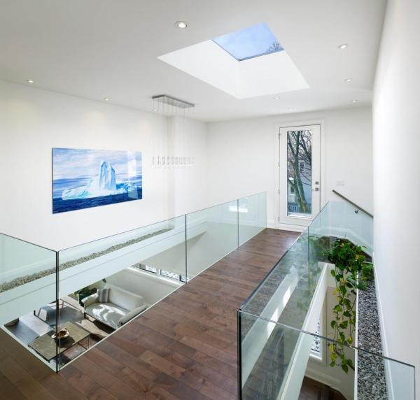 """Interior View from second floor bridge. Excessive heat that might be generated by large skylight or """"stack effect"""" has been avoided by offsetting the skylight at the higher floor level with combination of an opening whose play a role of a natural ventilation between the voids at the second floor, Image Courtesy © Tom Arban"""