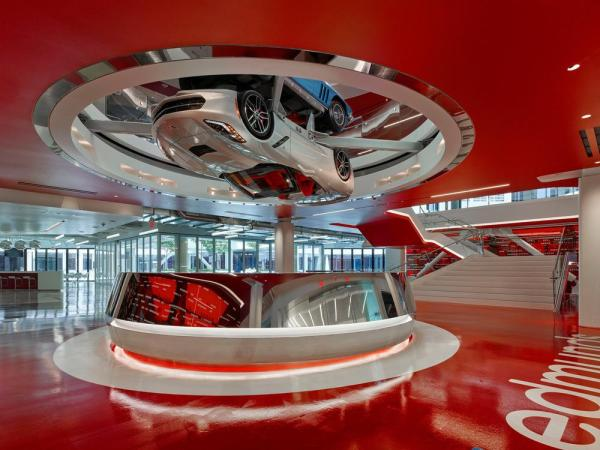 Polished mirror chrome reception desk at main arrivals lobby with main stair adjacent and 2016 Corvette Sting Ray turning above, Image Courtesy © Benny Chan @Fotoworks