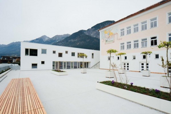 View of schoolyard with primary school and kindergarten, Image Courtesy © Bengt Stiller