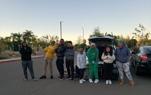 students posing in front of car