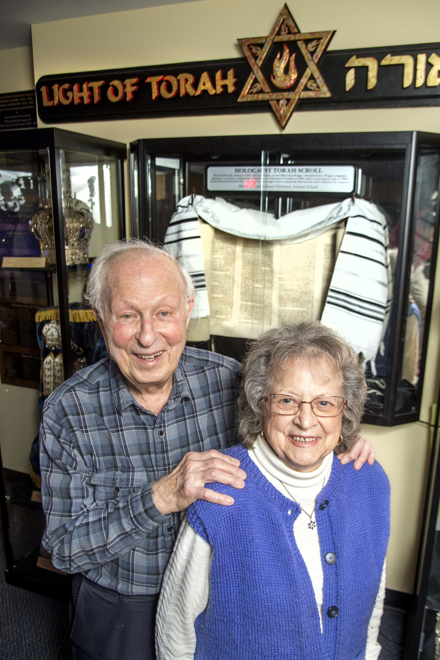 Sid Moszer and wife Eva, 88, with a display of torahs at Congregation Brothers of Israel in Newtown.