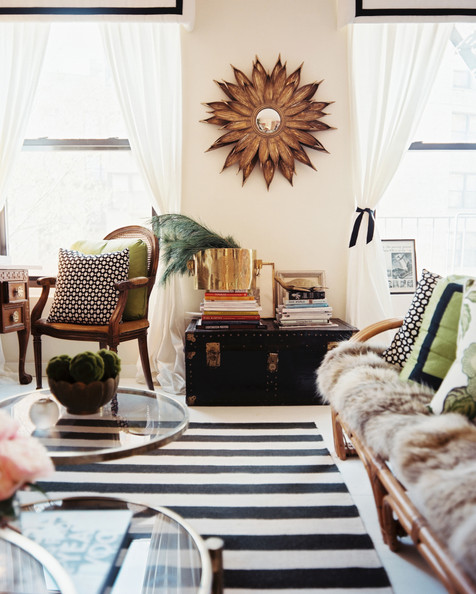 Bohemian Living Room - A gold starburst mirror framed by white curtains