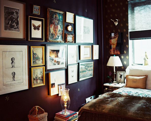 Bohemian - A gallery wall of art in a bedroom with a fur throw