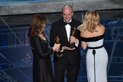 """Frances Hannon and Mark Coulier accept the Best Makeup & Hairstyling Award for """"The Grand Budapest Hotel"""" from Reese Witherspoon onstage during the 87th Annual Academy Awards at Dolby Theatre on February 22, 2015 in Hollywood, California."""