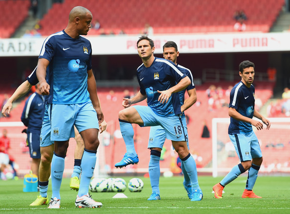 Vincent Kompany of Manchester City (L) and Frank Lampard of Manchester City warm up during the Barclays Premier League match between Arsenal and Manchester City at Emirates Stadium on September 13, 2014 in London, England.