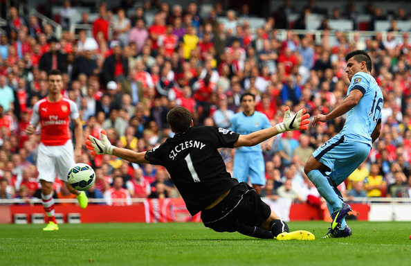Sergio Aguero of Manchester City scores the opening goal past Wojciech Szczesny of Arsenal during the Barclays Premier League match between Arsenal and Manchester City at Emirates Stadium on September 13, 2014 in London, England.