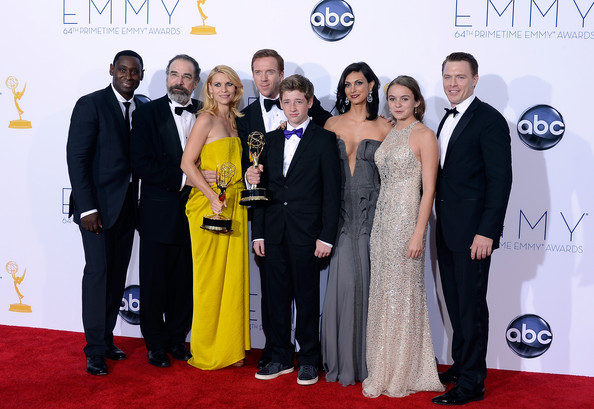 """Damian Lewis (L-R) Actors David Harewood, Mandy Patinkin, Claire Danes, Damian Lewis, Jackson Pace, Morena Baccarin, Morgan Saylor and Diego Klattenhoff, winners Outstanding Drama Series for """"Homeland,"""" pose in the press room during the 64th Annual Primetime Emmy Awards at Nokia Theatre L.A. Live on September 23, 2012 in Los Angeles, California."""