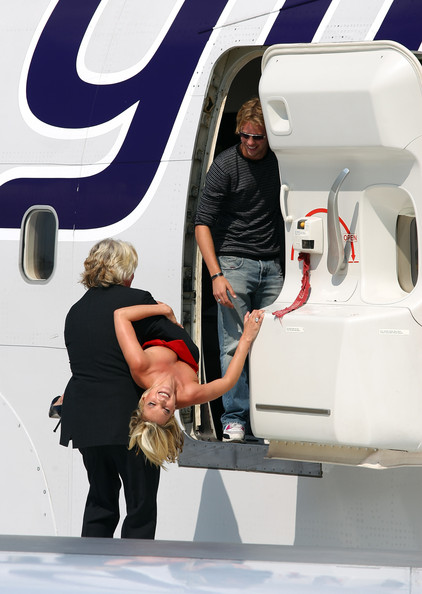 Sam Branson Virgin Atlantic boss Sir Richard Branson carries model Kate Moss on a wing of a jumbo jet while Sam Branson watches at Heathrow Airport on June 22, 2009 in London, England. Today Virgin Atlantic celebrates its 25th Birthday.