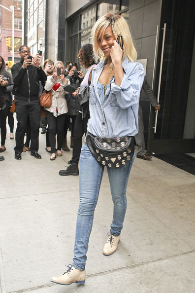 Rihanna Rihanna, wearing blue jeans, a denim shirt, denim bustier and dollar sign fanny pack, leaves her New York City hotel on her way to a photo shoot.
