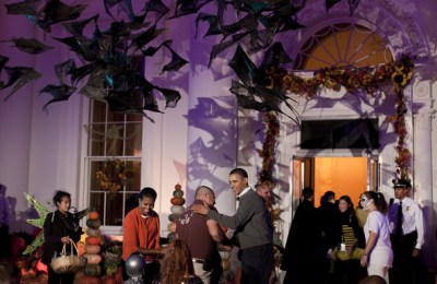 First lady Michelle Obama (C-Left) and U.S. President Barack Obama (C-Right) greet trick or treaters and their parents at the White House October 31, 2010 in Washington, DC. The Obama's greeted children and military families at the North Portico to celebrate Halloween and to trick or treat across the North Lawn.