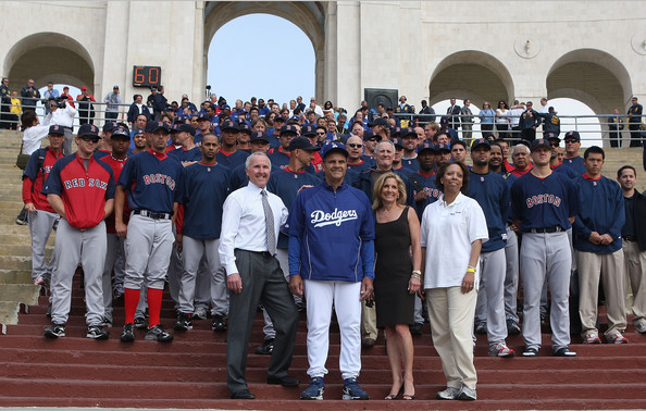 (L-R)Owner Frank McCourt, manager Joe Torre, owner Jamie McCourt of the Los Angeles Dodgers and Think Cure president Janet Clayton escort the Dodgers and the Boston Red Sox into the Los Angeles Memorial Coliseum before the game on March 29, 2008 in Los Angeles, California.