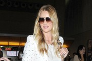 Model Rosie Huntington-Whiteley arriving on a flight at LAX in Los Angeles, California on August 22, 2014. The model traveled in her cool, causal style pairing a patterned blazer with distressed jeans.