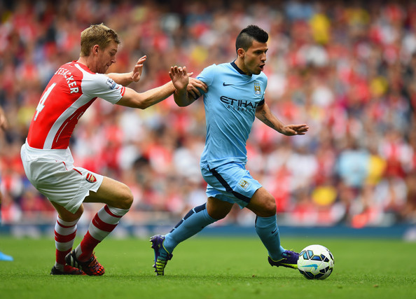 Sergio Aguero of Manchester City shrugs off a challenge from Per Mertesacker of Arsenal during the Barclays Premier League match between Arsenal and Manchester City at Emirates Stadium on September 13, 2014 in London, England.