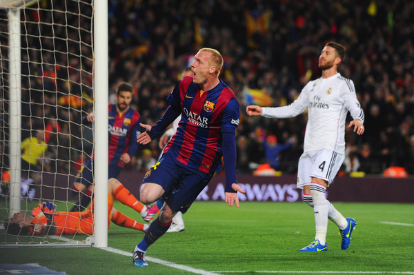 Sergio Ramos of Real Madrid CF (4) reacts as Jeremy Mathieu of Barcelona celebrates as he scores their first goal with a header during the La Liga match between FC Barcelona and Real Madrid CF at Camp Nou on March 22, 2015 in Barcelona, Spain.
