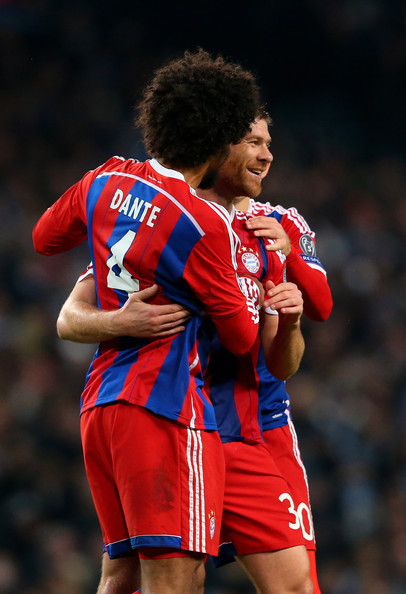 Xabi Alonso (R) of Bayern Muenchen is congratulated by teammateDante (L) after scoring a goal to level the scores at 1-1 during the UEFA Champions League Group E match between Manchester City and FC Bayern Muenchen at the Ethad Stadium on November 25, 2014 in Manchester, United Kingdom.