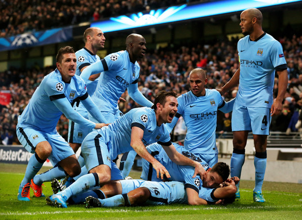 Sergio Aguero #16 (on ground) of Manchester City celebrates with teammates after scoring his team's third and matchwinning goal during the UEFA Champions League Group E match between Manchester City and FC Bayern Muenchen at the Etihad Stadium on November 25, 2014 in Manchester, United Kingdom.