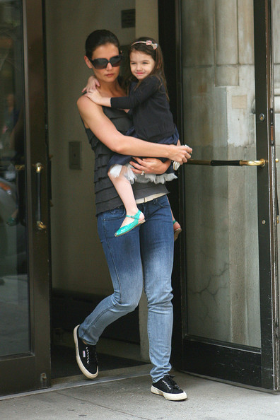 Katie Holmes and daughter Suri Cruise are spotted as they leave their New York City apartment building. Suri, who was carried by her mom, was wearing a frilly blue dress, a black blazer and pink bow in her hair.