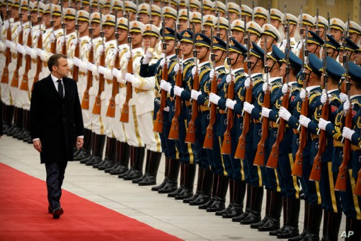 French President Emmanuel Macron reviews a Chinese honor guard during a welcome ceremony at the Great Hall of the People in…