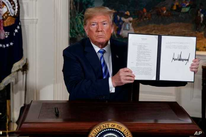 FILE - In this May 8, 2018 file photo President Donald Trump shows a signed Presidential Memorandum after delivering a…