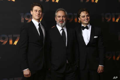 Actor George MacKay, from left, director Sam Mendes and actor Dean-Charles Chapman pose for photographers