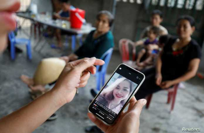 A relative looks at an image of Anna Bui Thi Nhung, a victim who was found dead in the back of British truck last month, at her…