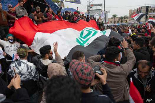 Anti government protesters carry a big Iraqi flag and chant anti Iran and anti U.S. slogans during the ongoing protests in…