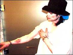 Michael Jackson shows his arm which he claims was injured by handcuffs when arrested.
