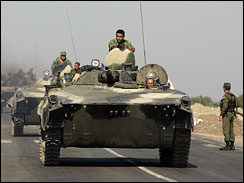 Russian armored vehicles move on the main highway connecting east and west, in Orjosani, northwest of the capital Tbilisi, Georgia, Tuesday, Aug. 19, 2008. A small column of Russian tanks and armored vehicles left the strategic Georgian city of Gori in the first sign of a Russian pullback of troops from Georgia after a cease-fire intended to end fighting that reignited Cold War tensions.