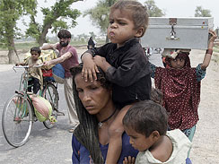 Members of Pakistani flood affected family flee their homes due to flooding in Muzaffargarh in central Pakistan Saturday, Aug. 14, 2010.