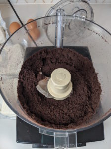Chocolate cookie crumbs sitting in a food processor and 3 large eggs on the counter