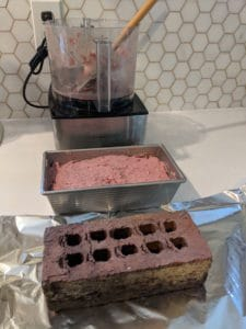 brick sitting on top of aluminum foil on kitchen counter in front of a loaf pan full of ground lamb and ground beef mixture in front of food processor on white countertop and white hexagonal backsplash
