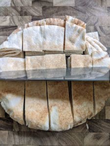 Pita bread cut into squares with chef knife on top of wood grain cutting board
