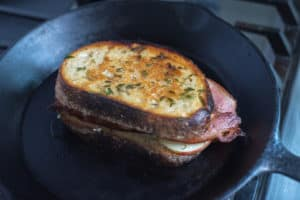 camembert grilled cheese with bacon apple and thyme cooking on the stove in a cast iron skillet.