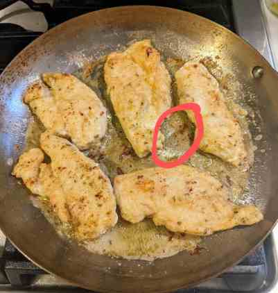 sauté pan white golden pan-fried chicken breasts cooking in olive oil and butter. Red circle around the brown sucs in the bottom of the pan