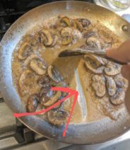 sauté pan with rich marsala wine sauce and mushrooms. Red arrow pointing to line drawn in sauce with wooden spatula