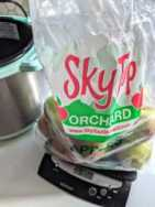 sky top orchard bag full of apples sitting on top of scale with 5 lbs 2 oz on the display sitting next two a teal instant pot