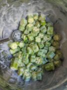 steel mixing bowl filled with sliced okra covered with egg and buttermilk mixture with spoon in bowl
