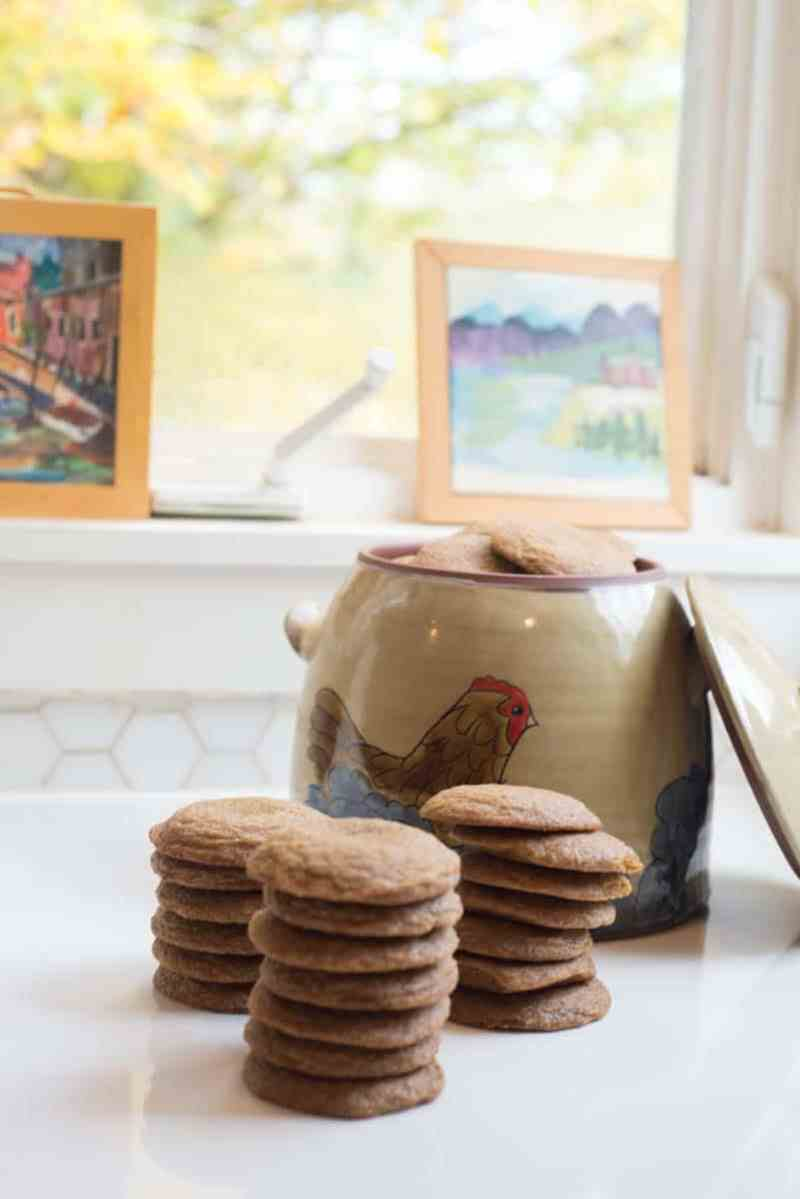 ginger molasses cookies on a white countertop in front of a pottery cookie jar with a hen in front of pretty windowsill with autumn leaves outside