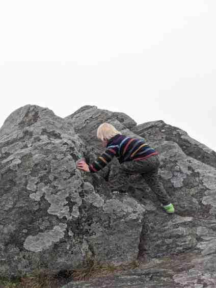 little boy in striped jacket rock climbing