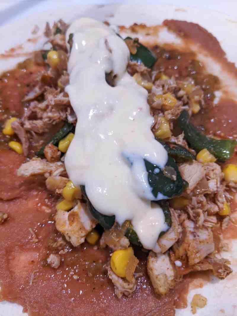 open face chicken enchilada with refried beans, corn, poblanos and cheese sauce