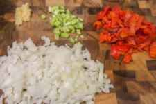 chopped onion, celery and roasted red peppers along with minced garlic prepped on a wood cutting board
