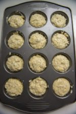 12 cup muffin pan filled with lemon poppy seed muffin batter