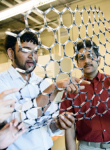 Podila and Rao hold a large-scale model of a sheet of graphene.