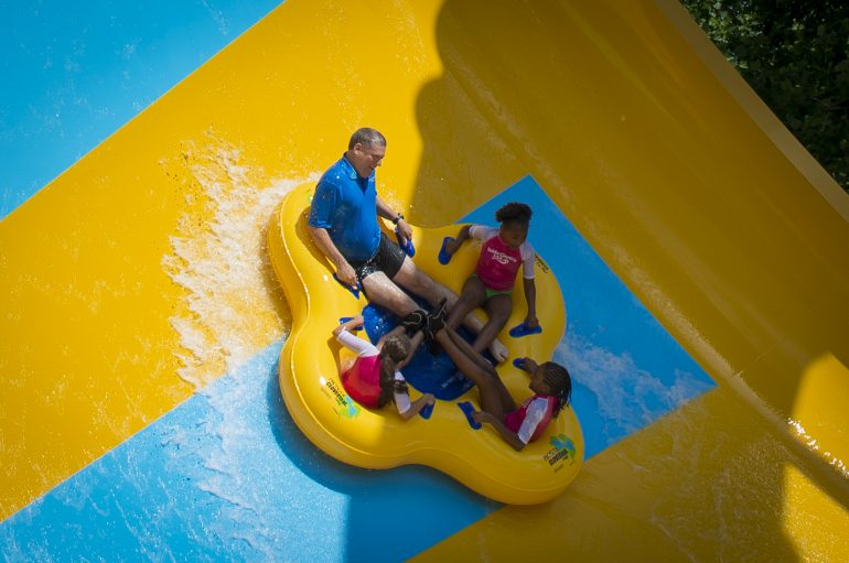 Park President Carl Lum and three fifth-graders from An Achievable Dream take one of the first trips down Colossal Curl. (WYDaily/Courtesy of SeaWorld Parks & Entertainment)