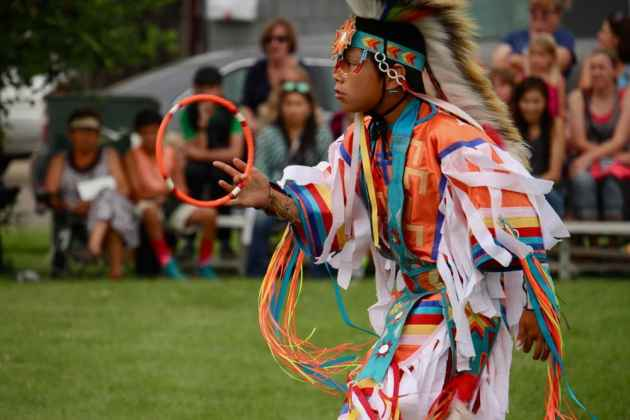 Sodizin Medicine Bull (Northern Cheyenne, Navajo, and Arapaho) spins a hoop during while wearing grass dance regalia during the First People's Powwow at the Sheridan Inn Thursday. The 10-year old dancer is from Ashland, Montana. (Gregory Nickerson/WyoFile)