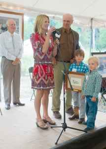 Kathy Lynch and sons Max and Will receive the rising-star award for their late husband and father Luke Lynch at a ceremony at the Murie Center on Thursday. John Turner, background. former director of the U.S. Fish and Wildlife Service received the Murie Spirit of Conservation Award. Center director Paul Hansen, center, announced the merger of the center and Teton Science Schools at the ceremony. (Angus M. Thuermer Jr./WyoFile)